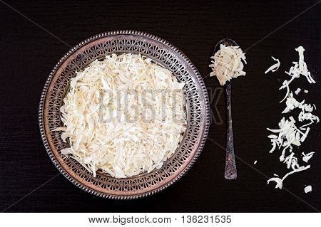 Dried onion flakes in a vintage metal bowl on a dark wooden table.
