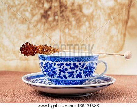 Blue pattern painted vintage cup of tea with brown sugar stirrer on top