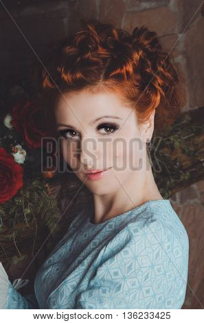 Portrait of beautiful red head woman with wavy hairstyle, smoky eyes makeup, blue retro dress, looking away in dark interior with red rose flower. Thoughtful young female in photo shoot studio.