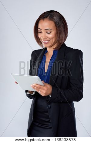 Beautiful mixed race woman browsing reading on her electronic tablet device, connected wirelessly
