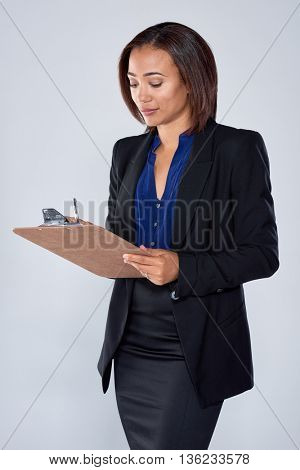Beautiful indian hispanic latino mixed race corporate business woman writing into an organiser, keeping notes