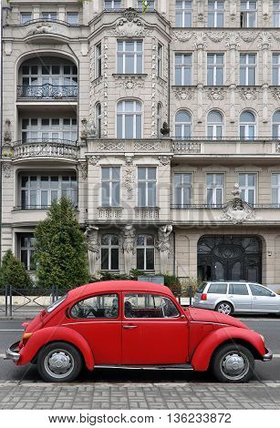 Wroclaw, Poland - April 4, 2016: Red car background Beetle on white classic old building with decor. Street in Wroclaw, Poland.
