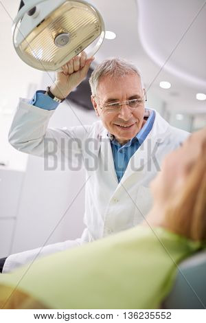 Male dentist adjust searchlight to illumine patient's mouth