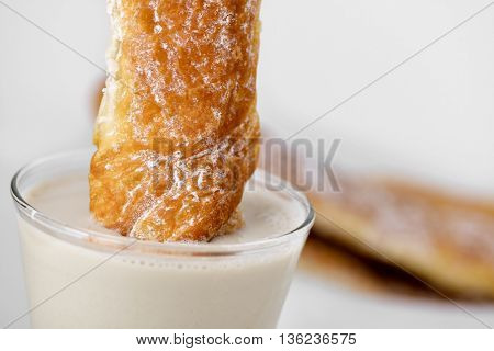 a farton soaked in a glass with horchata, a typical snack in Valencia, Spain