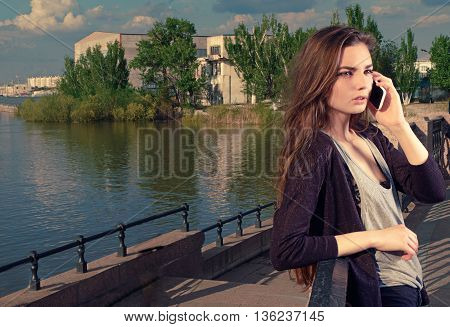 Young woman talking on her mobile phone listening to the conversation with a serious expression, she stands outdoors on granite embankment against a river backdrop, toned image, a lot of copyspace.