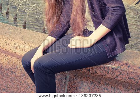 Mid section of body young woman sitting on red granite fountain and waiting for meeting. Toned shot, colorized image, instagram-like color filter.
