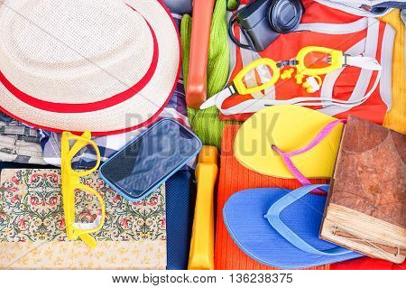 Travel suitcase full of holiday items view from above - Open case with clothes and summer vacation colorful objects - Concept of luggage packing with personal belonging for traveling