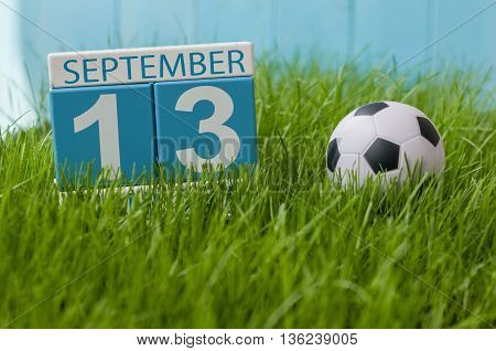 September 13th. Image of september 13 wooden color calendar on green grass lawn background. Autumn day. Empty space for text.