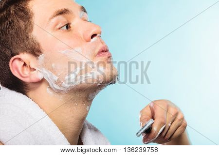 Young Man Shaving Using Razor With Cream Foam.