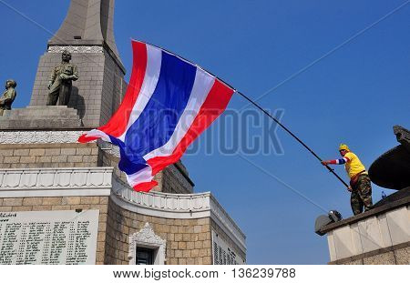 Bangkok Thailand - January 16 2014: Protestor waving a giant Thai flag standing on the Victory Monument during the Shut Down Bangkok demonstrations *