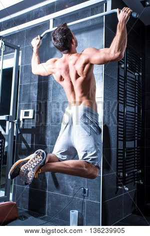 A young man doing pull ups in the Gym.