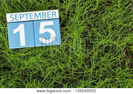 September 15th. Image of september 15 wooden color calendar on green grass lawn background. Autumn day. Empty space for text.