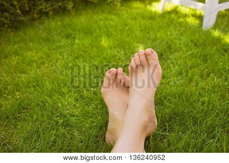 Close up of female crossed legs lying on the grass in a park.