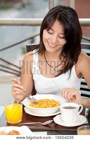 Beautiful woman eating her breakfast at home