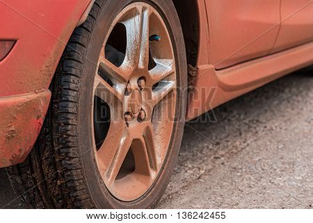 Dirty wheel of red car in country