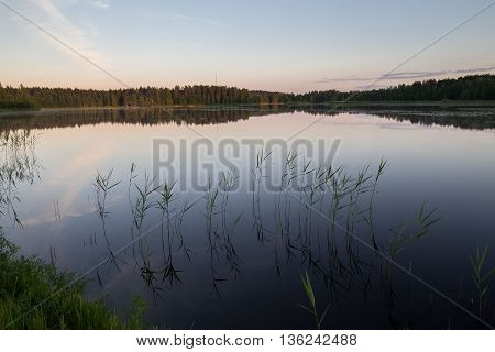 Beautiful sunset over calm lake in Mazury lake district. After sunset sky reflecting in water, calm vibrant landscape.