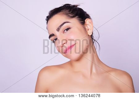 Closeup portrait of beautiful hispanic woman smiling. Latina model isolated over grey background.