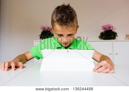 Surprised Boy Using White Tablet