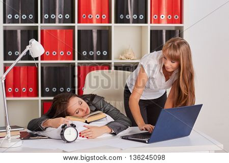 Tired young business woman is sleeping on workplace in the office, another employee took advantage of the situation and is stealing private information from computer of competitor.