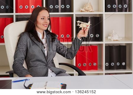 Businesswoman with a  model of plane sits on a workplace in the office. Travel agency.