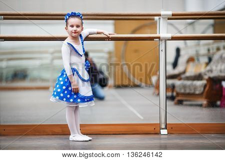 Child girl at a ballet school. Little girl ballerina posing at ballet barre. Happy girl in a dance class. Shallow depth of field. Selective focus.