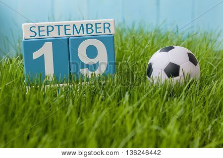 September 19th. Image of september 19 wooden color calendar on green grass lawn background. Autumn day. Empty space for text.