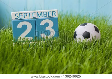 September 23rd. Image of september 23 wooden color calendar on green grass lawn background. Autumn day. Empty space for text.
