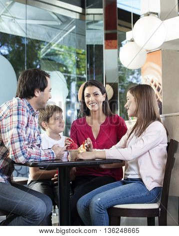 Happy Family Looking At Mother In Ice Cream Parlor