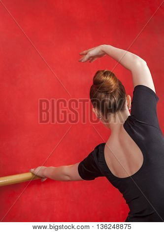Female Ballet Dancer Performing Against Red Wall