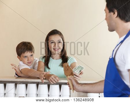 Siblings Paying For Chocolate Ice Cream To Waiter