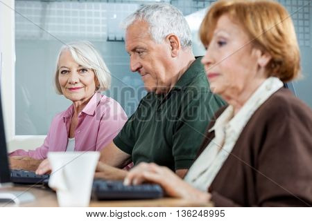 Confident Senior Woman With Classmates Using Computer In Classro