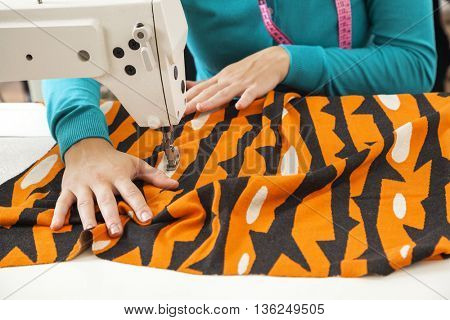 Tailor Sewing Fabric At Workbench In Factory
