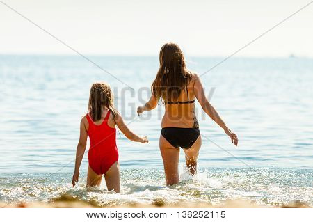 Little girl child and mother having fun in ocean. Kid and woman bathing in sea water. Summer vacation holiday relax.