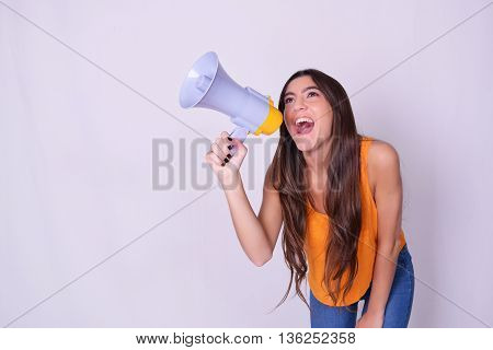 Young beautiful woman shouting through a megaphone or loudspeaker. Caucasian woman expressing. Leadership concept.