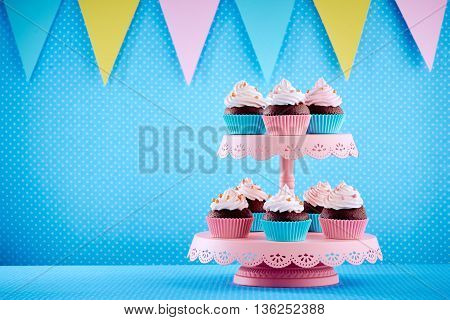 Decorated cupcakes on tray on the blue background