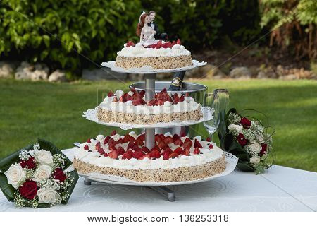 Three levels of wedding cake on the table in a garden