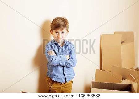 little cute boy in empty room, remoove to new house. home alone emong boxes close up kid
