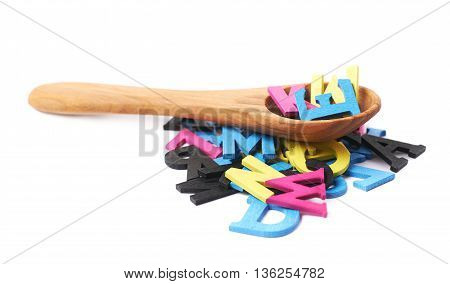 Pile of cmyk painted wooden letters with the wooden serving spoon over it, composition isolated over the white background