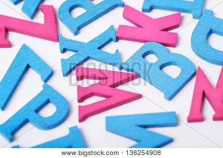 White surface covered with the multiple colorful blue and pink painted wooden letters as a backdrop composition
