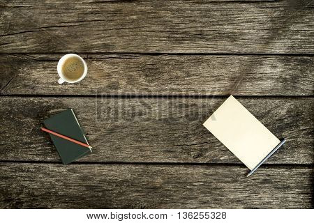 Overhead view of coffee notebook and blank piece of paper on textured wooden table.