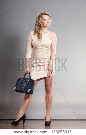 Confident Woman Withhand Bag And Black High Heels.