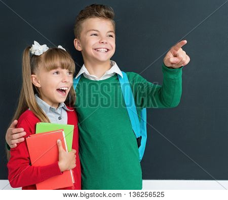 Happy cute boy and girl learning playfully in front of a big chalkboard