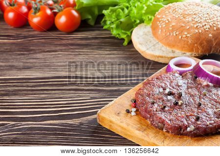 The raw ingredients for the homemade burger on brown wooden table.