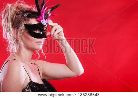 woman wearing elegant evening dress and carnival mask on red background