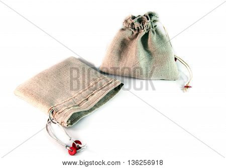 Two small sack with ties made of coarse linen cloth on white background. Not dyed fabric natural color
