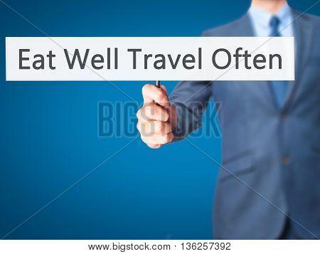 Eat Well Travel Often - Businessman Hand Holding Sign