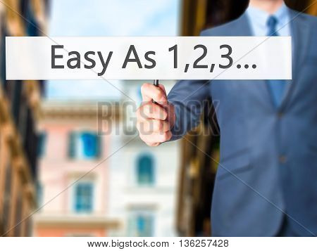 Easy As 1,2,3... - Businessman Hand Holding Sign