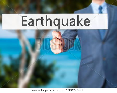 Earthquake - Businessman Hand Holding Sign