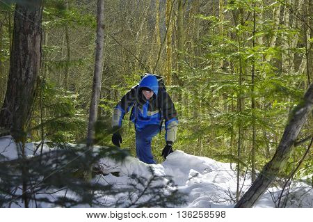man goes through the woods on snowshoes