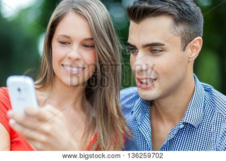 Young Smiling Couple Making A Self Portrait with a smartphone